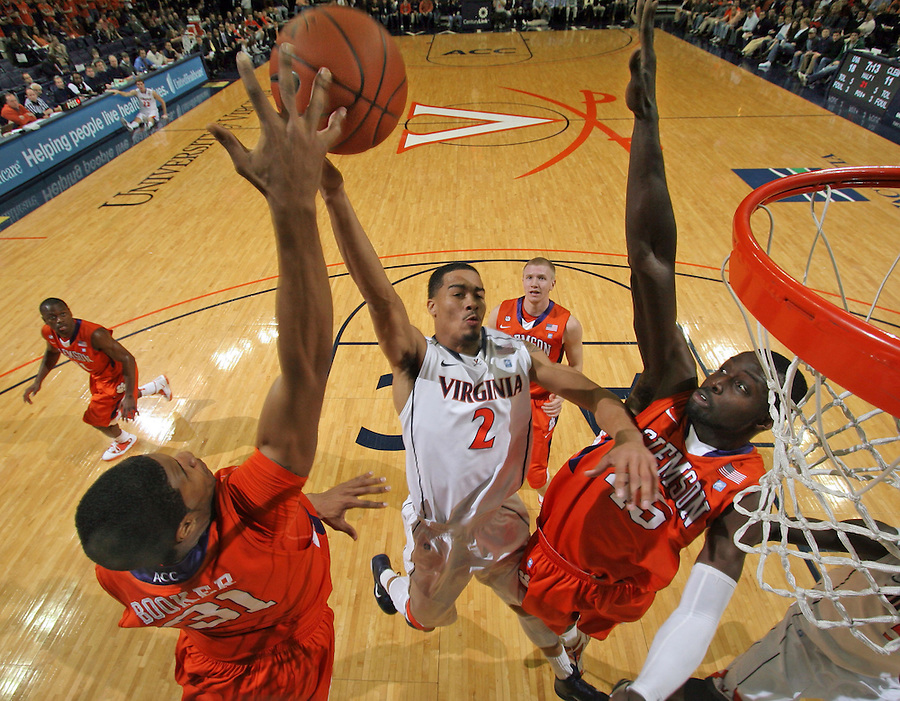 Feb. 2, 2011; Charlottesville, VA, USA; Virginia Cavaliers guard Mustapha Farrakhan (2) is defended by Clemson Tigers forward/center Devin Booker (31) and Clemson Tigers forward/center Jerai Grant (45) during the game at the John Paul Jones Arena. Mandatory Credit: Andrew Shurtleff