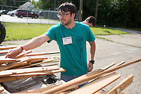 "Joseph Zongolowicz unloads wood from a truck as he and other members move it into a dumpster during ""Circle the City with Service,"" the Kiwanis Circle K International's 2015 Large Scale Service Project, on Wednesday, June 24, 2015, at the Friendship Westside Center for Excellence in Indianapolis. (Photo by James Brosher)"