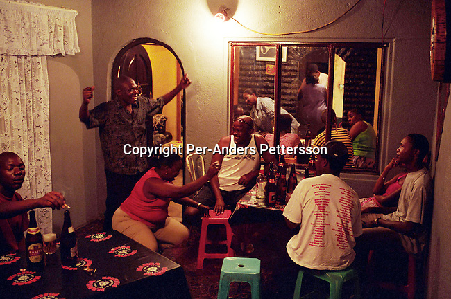 SOWETO, SOUTH AFRICA - FEBRUARY 28: Unidentified people partying at Tina's tavern on February 28, 2004, in Orlando West, Soweto, South Africa. These bars, known as shebeens, are found in almost every block in the townships. The bar is usually a part of the ownerÕs house and many people come and drink here daily, as they don't have work. .(Photo: Per-Anders Pettersson/Getty Images).....