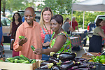 Monique Lohmeyer (center), a case manager for Church World Service, helps Casmil Ngundakumana (left) and Evanis Gatunzi, both refugees from Rwanda, navigate through the produce available in the Durham Farmers' Market in Durham, North Carolina. The market's Double Bucks program allows consumers with EBT cards to double their purchasing power.<br /> <br /> Church World Service resettles refugees in North Carolina and throughout the United States.<br /> <br /> Photo by Paul Jeffrey for Church World Service.