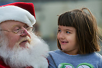 Santa Claus, portrayed by Santa Clarence, a member of the Amalgamated Order of Bearded Santas, listens as a girl explains her Christmas wishes outside a shipping store where he greeted young and old to hear their Christmas wishes.