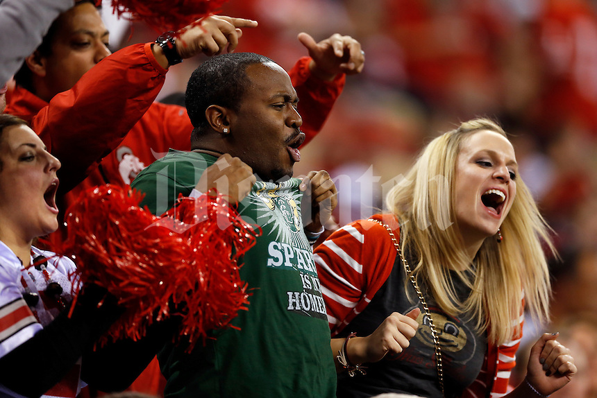Ohio State and Michigan State fans fight for tv time during the second quarter of the Big Ten championship football game at Lucas Oil Stadium in Indianapolis on Dec. 7, 2013. (Adam Cairns / The Columbus Dispatch)