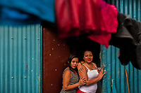 Salvadoran sex workers pose for a picture in front of a room where their sexual services are offered to clients in San Salvador, El Salvador, 12 April 2018. Although prostitution is not legal in El Salvador, dozens of street sex workers, wearing provocative miniskirts, hang out in the dirty streets close to the capital's historic center. Sex workers of all ages are seen on the streets but a significant part of them are single mothers abandoned by their male partners. Due to the absence of state social programs, they often seek solutions to their economic problems in sex work. The environment of street sex business is strongly competitive and dangerous, closely tied to the criminal networks (street gangs) that demand extortion payments. Therefore, sex workers employ any tool at their disposal to struggle hard, either with their fellow workers, with violent clients or with gang members who operate in the harsh world of street prostitution.