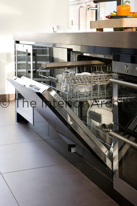 In the kitchen/living area a dishwasher is concealed behind the high-gloss finish of black parapan cupboard doors