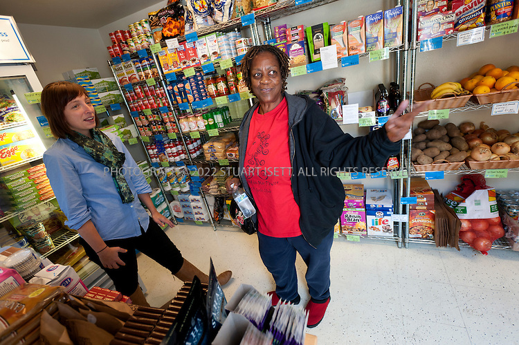 10/27/2011--Seattle, WA, USA..Debra Craig, 56, checks out the offerings at a Stockbox mini-store in Seattle, WASH...Started by Carrie Ferrence (SEEN LEFT)  and Jacqueline Gjurgevich, Stockbox has its first unit in the Delridge neighborhood in west Seattle. StockBox, which takes recycled shipping containers and turns them into mini grocery stores offering affordable fresh and healthier foods in areas underserved by grocery stores, hopes to place the shops in so-called food deserts...©2011 Stuart Isett. All rights reserved.