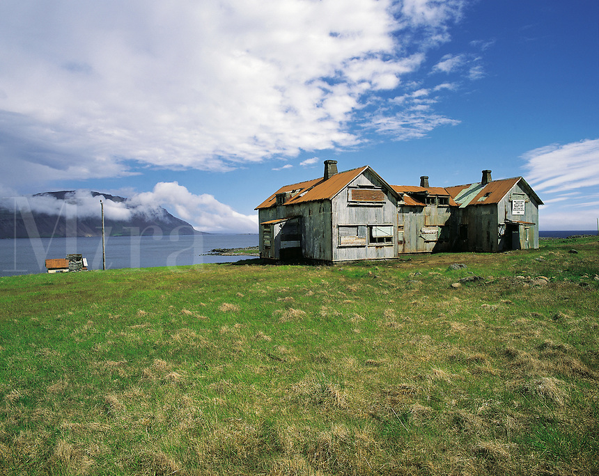 Old abandoned hospital with sea and distant misty hills behind at Faskrudfjord, south-east Iceland