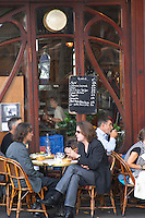 Le Bistrot du Peintre cafe bar terrasse terasse outside seating on the sidewalk. People sitting in chairs at tables eating and drinking outside at lunch time. An old chalk black board chalkboard blackboard with the menu written in white The Bistrot du Peintre is an old fashioned Paris café cafe bar restaurant of art nouveau design with polished brass, mirrors and old signs