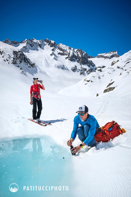 Water filter use in a small melt water pool while ski touring on the Berner Haute Route, Switzerland