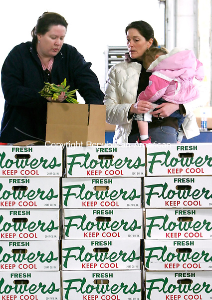 WATERTOWN, CT--19 MARCH 2007--031907JS01-Wendy Matthews of Middlebury, right, holds her daughter Lindsey as they wait for Trish Morrissey, Community Executive for Income Development for the Litchfield County chapter of the American Cancer Society, as she packs up daffodils to be delivered. 44,500 daffodils were delivered and sorted at the Fed-Ex facility in Watertown as part of the Cancer Society's annual Daffodil Days fundraiser. The flowers will be delivered to cancer paitents in Litchfield County by Fed-Ex. <br /> Jim Shannon / Republican-American