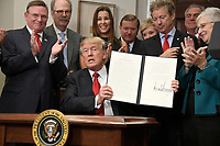 United States President Donald J. Trump shows an Executive Order to promote healthcare choice and competition in the Roosevelt Room of the White House in Washington, DC on Thursday, October 12, 2017.  The President's controversial plan is designed to make lower-premium health insurance plans more widely available.<br /> Credit: Ron Sachs / Pool via CNP /MediaPunch