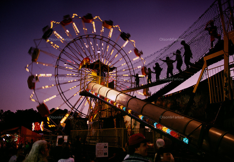 """At dusk, a glittering slide and spinning """"Skydiver"""" illuminate the Cullman County fairgrounds in Alabama. """"Folks come 44 miles up from Birmingham,"""" says fair manager Odie Johnson, """"just for the rides."""""""