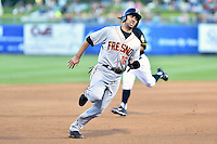 Travis Ishikawa (16) of the Fresno Grizzlies hustles towards third base against the Salt Lake Bees at Smith's Ballpark on May 25, 2014 in Salt Lake City, Utah.  (Stephen Smith/Four Seam Images)