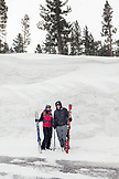 USA, California, Mammoth, a couple pauses near the tall snow bank on their way to the chairlift at Mammoth Lakes