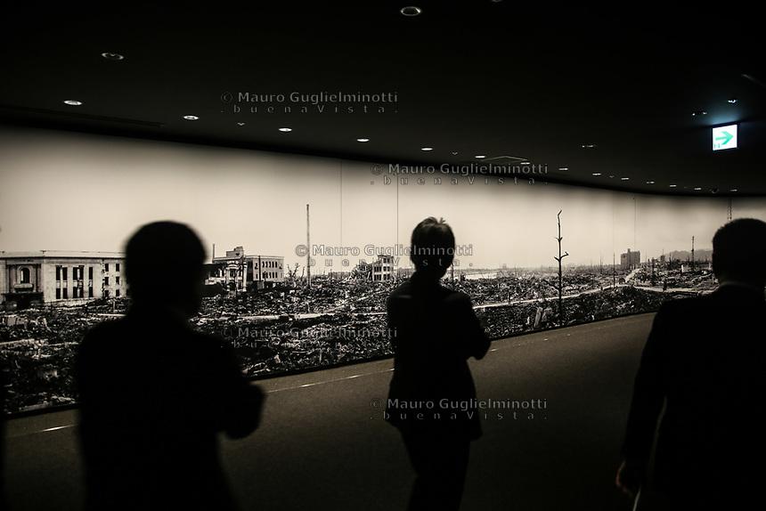 visitatori giapponesi osservano gli effetti dell'esplosione  japanese visitors looking at the explosion effects