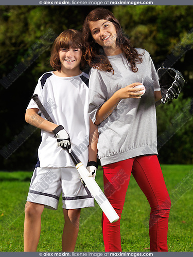 Portrait of two happy smiling children, brother and sister, 10 and 13, practicing baseball, active summer outdoor lifestyle.