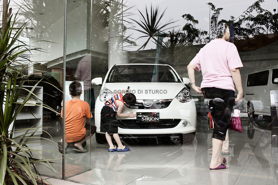 JAKARTA, INDONESIA, MAY 2013: Middle calss family looks for a new car in the<br /> Astra International Showroom in Sunter area, North of Jakarta, May 2013.<br /> <br /> © Giulio Di Sturco for Bloomberg Markets