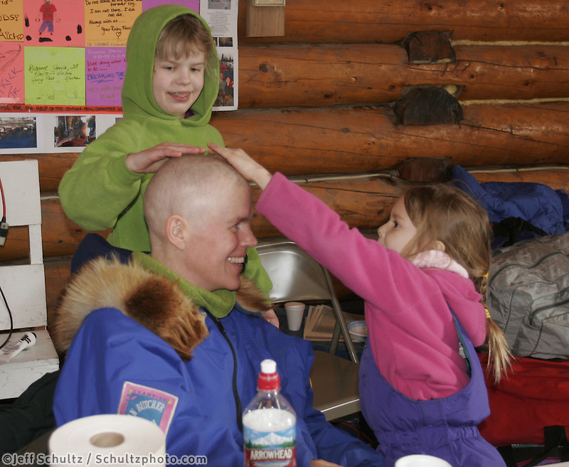 Susan Butcher's daughters rub her head at the Ruby checkpoint.  Susan, fighting Leukemia, is out spectating the race.