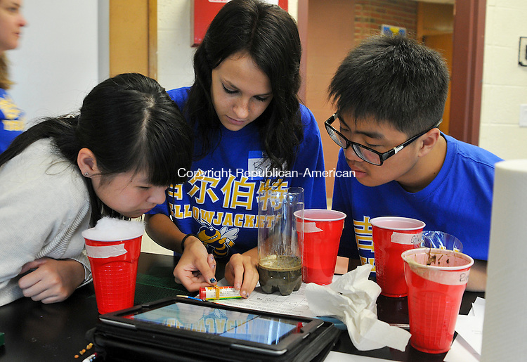 WINSTED, CT 30 JULY 2013--073013JS01--Briana Hall, an incoming sophomore at the Gilbert School in Winsted, center, along with visiting students from Jinhau No. 8 High School in China,  checks the ph levels in some water during  a lesson on water filtration and remediation at the school on Tuesday. The students are taking part in the first-ever summer camp for international students. <br /> Jim Shannon Republican American