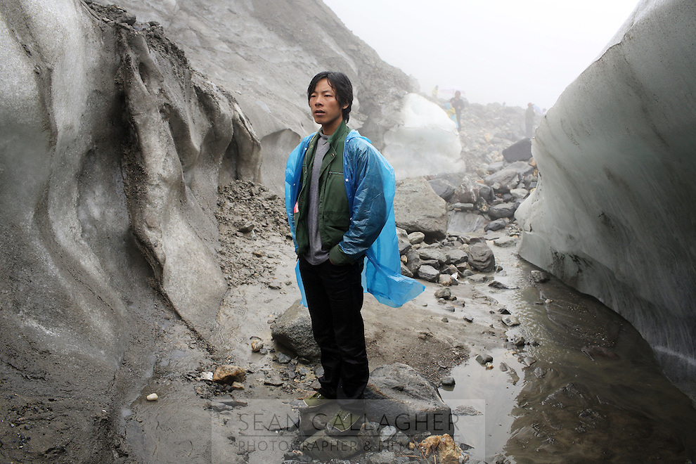 A local guide stands watch inside a crevasse in the lower reaches of the Hailuogou glacier in western Sichuan Province, China. As a result of rising temperatures on the Tibetan Plateau, the Hailuogou glacier has retreated over 2 km during the 20th century alone. Since the Little Ice Age, studies have revealed that the total monsoonal glacier coverage in the southeast of the Tibetan Plateau has decreased by as much as 30 percent, causing alarm in scientific circles.
