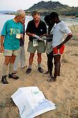 Kisamba Bay, Tanzania. Tourists on safari asking directions from local men.
