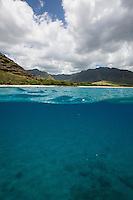 View of Waianae mountain range, Makua Bay and beach from above and below the water