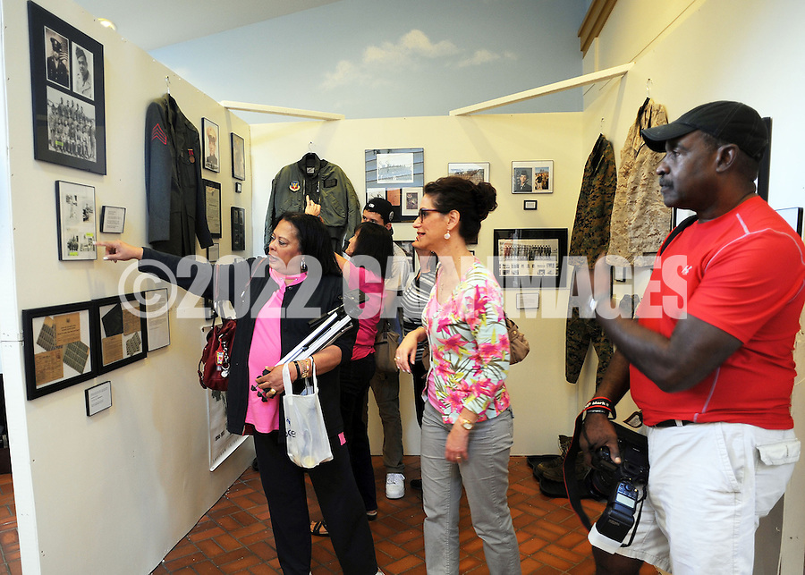 LOWER MAKEFIELD, PA - SEPTEMBER 20: Tanya Van Jones (L), Jean Green (C), and Vance Van Jones (R) look at a display featuring images of Tanya's father as part of a fund raiser for Wounded Warriors September 20, 2014 at Spring Village at Floral Vale in Lower Makefield, Pennsylvania. (Photo by William Thomas Cain/Cain Images)