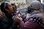 A woman administers an inhaler to a protester overcome with tear gas on Mohamed Mahmoud Street near Tahrir Square in Cairo, Egypt, Tuesday, November 22, 2011. Clashes between Central Security Forces and demonstrators demanding an end to military rule continued into a fourth day.