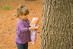 Toddler playing with doll baby under pine tree.