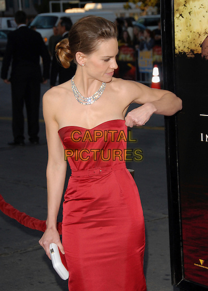 "HILARY SWANK .The Warner Brothers' Pictures L.A. Premiere of ""The Reaping"" held at The Mann Village Theatre in Westwood, California, USA..March 29th, 2007.half length red strapless dress belt adjusting hand gesture profile diamond necklace white clutch purse  .CAP/DVS.©Debbie VanStory/Capital Pictures"