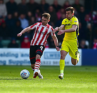 Lincoln City's Lee Frecklington vies for possession with Cheltenham Town's Kevin Dawson<br /> <br /> Photographer Andrew Vaughan/CameraSport<br /> <br /> The EFL Sky Bet League Two - Lincoln City v Cheltenham Town - Saturday 13th April 2019 - Sincil Bank - Lincoln<br /> <br /> World Copyright &copy; 2019 CameraSport. All rights reserved. 43 Linden Ave. Countesthorpe. Leicester. England. LE8 5PG - Tel: +44 (0) 116 277 4147 - admin@camerasport.com - www.camerasport.com