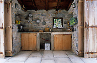 The rustic kitchen has folding doors on either side to take advantage of the sea breeze