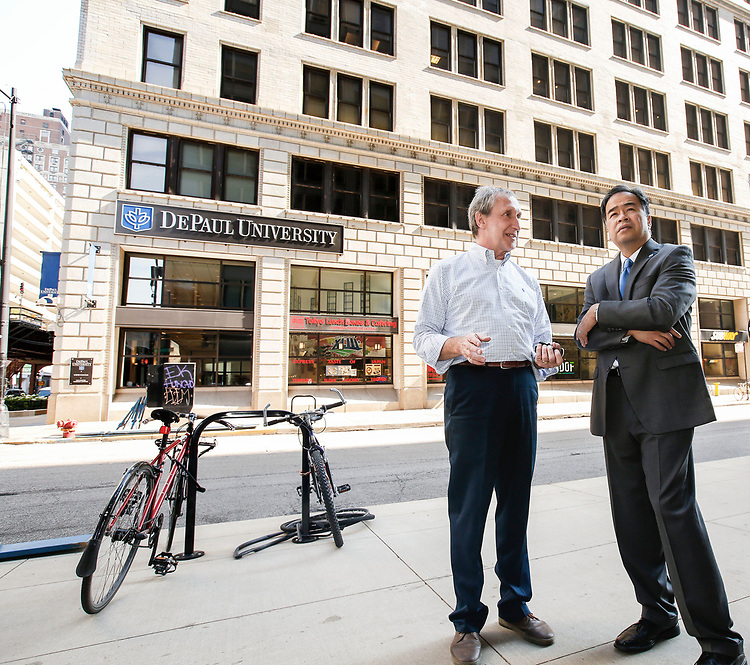 Standing at the intersection of Jackson Blvd. and Wabash Ave., Bob Janis, left, vice president of facility operations, offers DePaul President A. Gabriel Esteban, Ph.D., a tour of the Loop Campus Wednesday, July 5, 2017. Dr. Esteban and his wife spent an hour getting acquainted with some of the university's spaces and faces in the Loop during his first week on the job. (DePaul University/Jamie Moncrief)