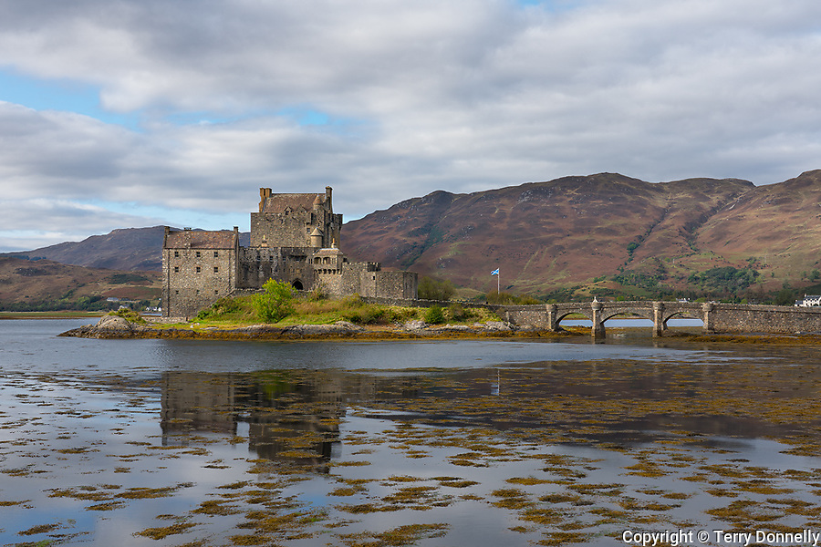 Western Highlands, Scotland:<br /> Eileen Donan Castle and reflections under clouded sky, Kintail National Scenic Area