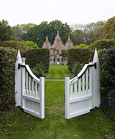 A painted wooden garden gate leads from the rear of the house to a meadow beyond