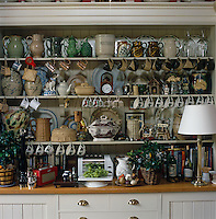 A large collection of cups and crockery is crammed on the shelves of a traditional Welsh dresser