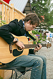 ALASKA, Talkeetna, a young man Ian Merkley plays the guitar on the street in town
