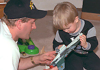 Father and son playing airplane at birthday party ages 35 and 3.  Brooklyn Center  Minnesota USA