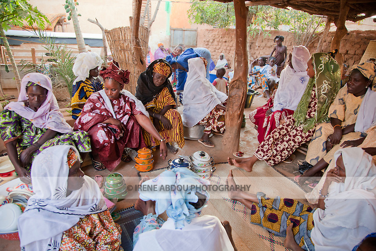 In the town of Djibo in northern Burkina Faso, a wedding has taken place.  Friends and family of the bride carry gifts and possessions of the bride - pots and pans, blankets, textiles, and other items - from the bride's home to her new home with her husband.  Surprisingly, many of these gifts are not destined for the bride or groom, but are being parceled out to wedding guests and relatives of the groom.