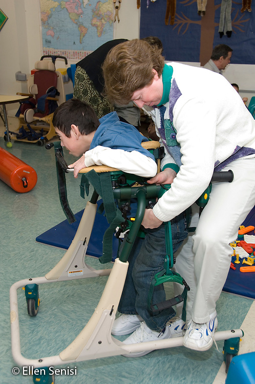 MR / Albany, NY.Langan School at Center for Disability Services .Ungraded private school which serves individuals with multiple disabilities.Physical therapist positions child in gait trainer. Boy: 11, cerebral palsy, expressive and receptive language delays.MR: Bro12; Pie3.© Ellen B. Senisi