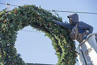 NWA Democrat-Gazette/J.T. WAMPLER Matt Canada of Lincoln hangs a large wreath over Walnut Street in Rogers Monday Nov. 26, 2018. A crew from Lighting Master has spent the last two weeks decorating downtown Rogers for the holidays.