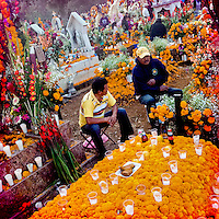 Mexican men sit around a grave, covered by marigold flowers, honouring their deceased relatives during the ritual celebration of the Day of the Dead (Día de Muertos) at the cemetery of Tzurumútaro, Michoacán, Mexico, 2 November 2014.