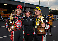 Oct 14, 2018; Concord, NC, USA; NHRA top alcohol dragster driver Megan Meyer (left), top fuel driver Steve Torrence (right) and his mother Kay Torrence celebrate after winning the Carolina Nationals at zMax Dragway. Mandatory Credit: Mark J. Rebilas-USA TODAY Sports