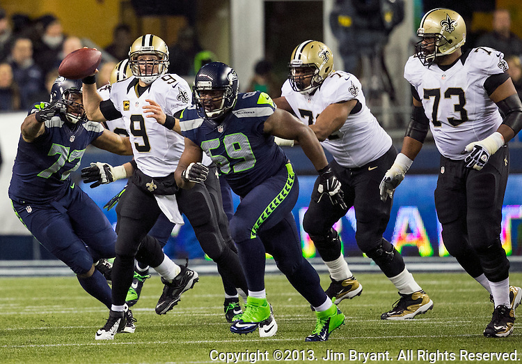 New Orleans Saints quarterback Drew Brees (8) is pressured while trying to pass against the Seattle Seahawks during the third quarter at CenturyLink Field in Seattle, Washington on December 2, 2013.  The Seahawks became the first team to clinch a spot in the NFC playoffs with a 34-7 victory over the New Orleans Saints.  Brees completed 23 of 38 passes for 147 yards in the loss. ©2013. Jim Bryant Photo. ALL RIGHTS RESERVED.