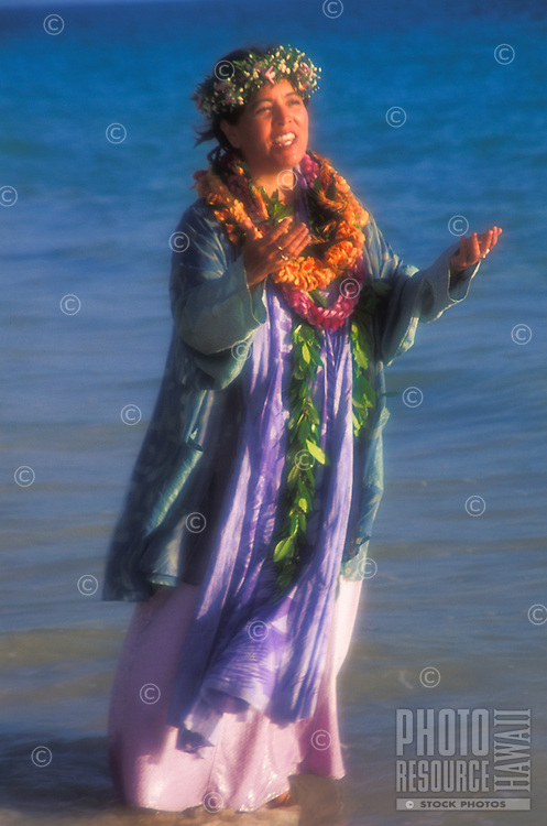 Hawaiian woman in leis chanting (oli) at sunrise at Lanikai beach, Oahu