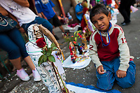 A Mexican boy, a worshipper of Santa Muerte (Saint Death) makes his altar in front of the shrine in Tepito, a dangerous neighborhood of Mexico City, Mexico, 1 May 2011. The religious cult of Santa Muerte is a syncretic fusion of Aztec death worship rituals and Catholic beliefs. Born in lower-class neighborhoods of Mexico City, it has always been closely associated with crime. In the past decades, original Santa Muerte's followers (such as prostitutes, pickpockets and street drug traffickers) have merged with thousands of ordinary Mexican Catholics. The Saint Death veneration, offering a spiritual way out of hardship in the modern society, has rapidly expanded. Although the Catholic Church considers the Santa Muerte's followers as devil worshippers, on the first day of every month, crowds of believers in Saint Death fill the streets of Tepito. Holding skeletal figurines of Holy Death clothed in a long robe, they pray for power healing, protection and favors and make petitions to 'La Santísima Muerte', who reputedly can make life-saving miracles.