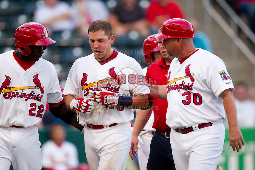 Travis Tartamella (29) of the Springfield Cardinals is escorted back to the dugout by Jermaine Curtis (22) and hitting coach Phillip Wellman (30) after being hit in the face by a pitch during a game against the Arkansas Travelers at Hammons Field on July 25, 2012 in Springfield, Missouri. (David Welker/Four Seam Images)