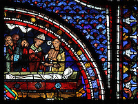 The body of Lazarus is wrapped in a shroud and a bishop and cleric preside over the ceremony, from the funeral of Lazarus, from the Life of Mary Magdalene stained glass window, 13th century, in the nave of Chartres cathedral, Eure-et-Loir, France. Chartres cathedral was built 1194-1250 and is a fine example of Gothic architecture. Most of its windows date from 1205-40 although a few earlier 12th century examples are also intact. It was declared a UNESCO World Heritage Site in 1979. Picture by Manuel Cohen