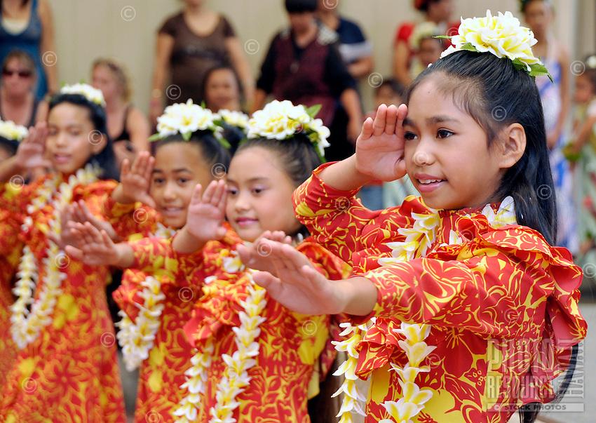 Young girls wearing yellow plumeria lei perform hula at Ward Warehouse shopping center in Honolulu, O'ahu