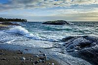 Brytande våg vid  klippa på havsstrand vid Torö i Stockholms skärgård