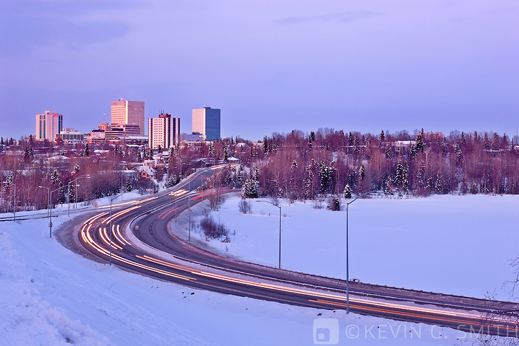 Winter sunset light falls on the downtown Anchorage Skyline overlooking Westchester Lagoon with traffic on Minnesota Blvd. Winter, Southcentral Alaska, USA.